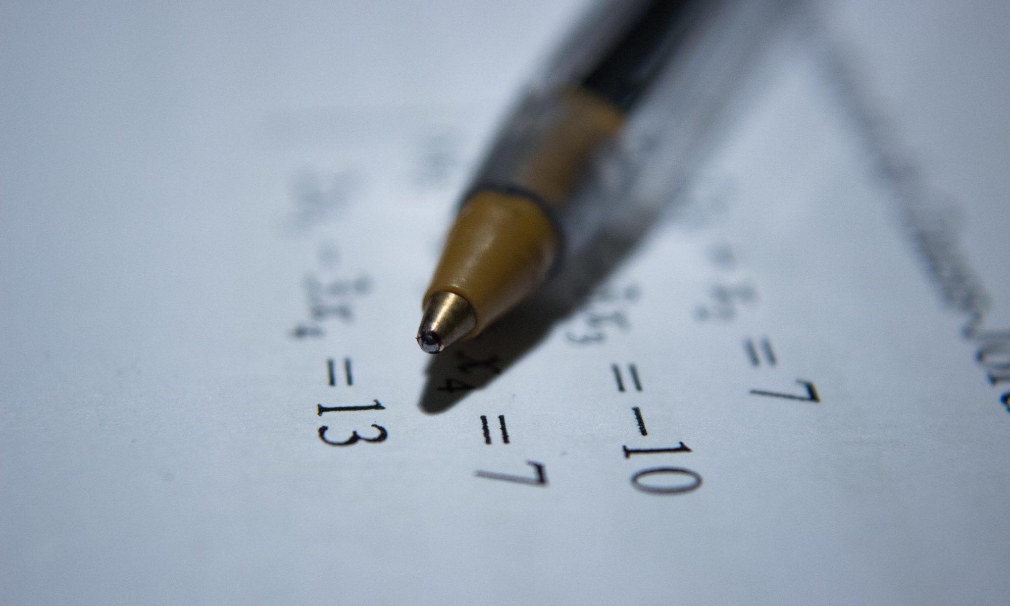 Caneta sobre papel com os cálculos da aposentadoria 86/96 ao fundo
